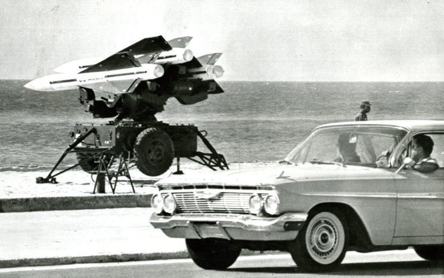 "October 27, 1962 / US Army antiaircraft rockets were mounted on launchers and pointed out over the Florida Straits in full view of the public at Key West, Florida. These rockets in position on a formerly public beach are viewed from automobiles driving along Roosevelt Boulevard. The rocket positions are manned day and night. Off-duty missilemen sleep in sleeping bags on the beach while other soldiers walk guard duty with rifles. ""We're trained to perfection and ready to go,"" one soldier reported to newsmen."